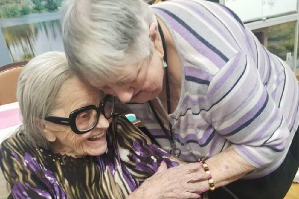 Two residents hugging at Legacy Oaks of Sacramento in Sacramento, California