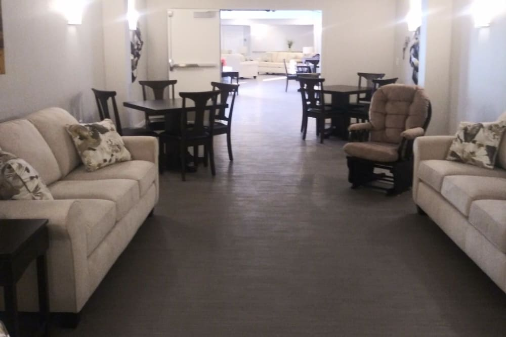 Community space with couches, tables and chairs at Arlington Place of Red Oak in Red Oak, Iowa