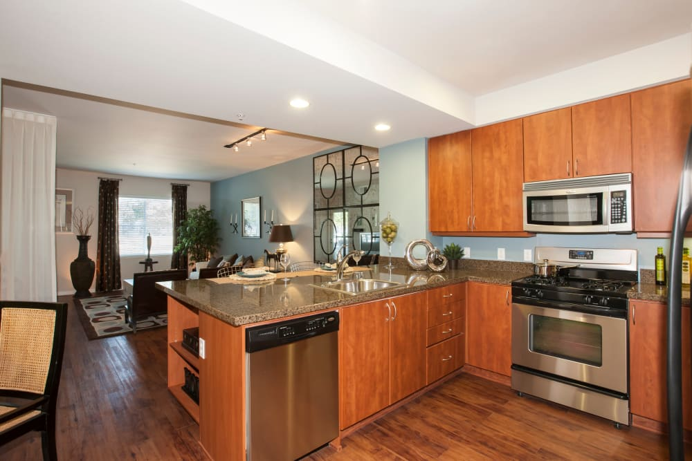 Kitchen with distressed faux-hardwood flooring and natural colored cabinetry at Azure Apartment Homes in Petaluma, California