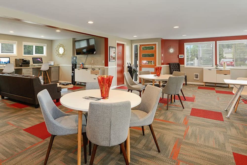 Multiple tables with chairs in community clubhouse at Terra Apartment Homes in Federal Way, Washington