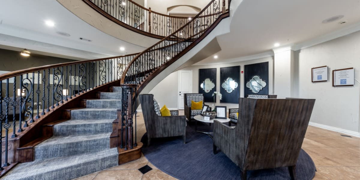 Lobby entrance with sitting area and stairs leading up to clubhouse amenities at Marquis at Stone Oak in San Antonio, Texas