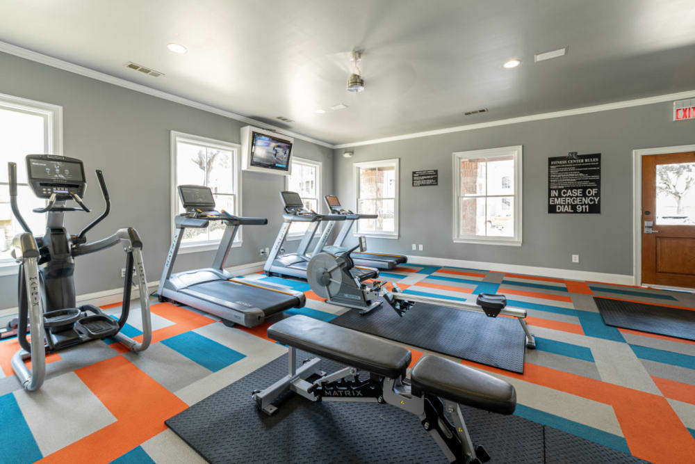 Treadmills, row machine, elliptical, and TV monitor in fitness room at Marquis at Bellaire Ranch in Fort Worth, Texas
