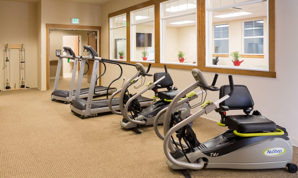 Treadmills and rowers in the gym at Quail Park of Lynnwood in Lynnwood, Washington