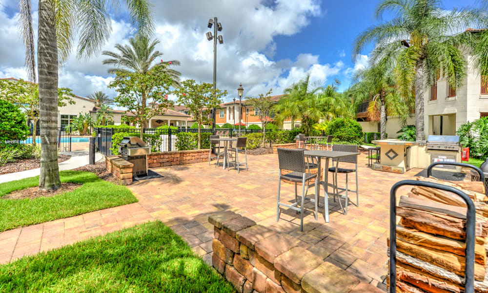 Well-manicured landscaping around the barbecue area with gas grills at Hacienda Club in Jacksonville, Florida