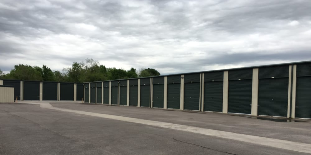 Outdoor storage units with green doors at StorQuest Self Storage in Richmond, Texas
