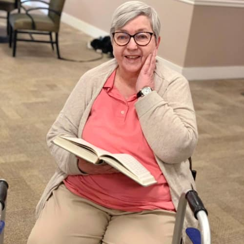 A smiling resident reading a book at FountainBrook in Midwest City, Oklahoma