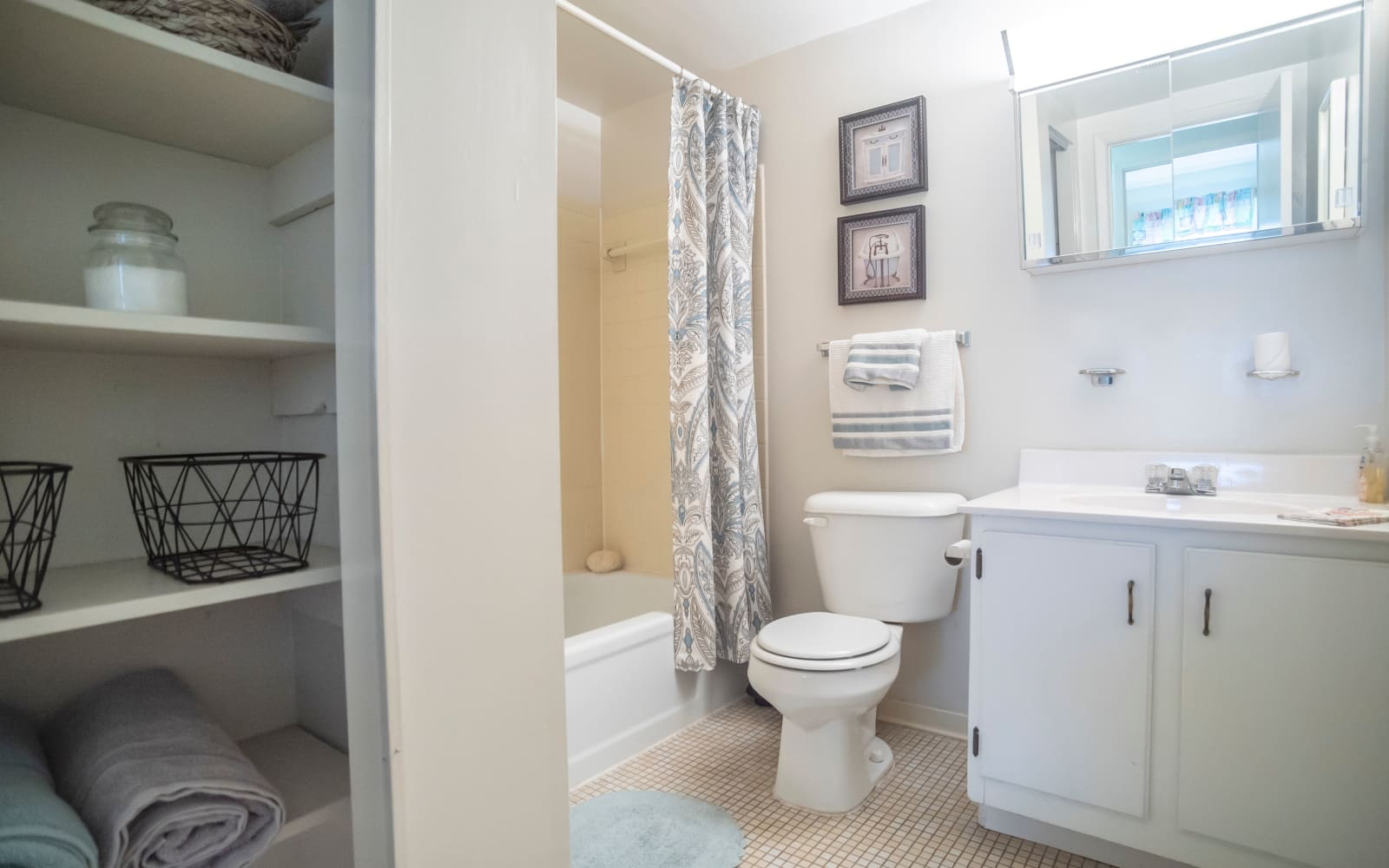 Bathroom with storage space for towels at Hunt Club Apartments in Cockeysville, Maryland