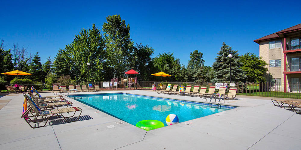 Swimming pool with sundeck and lounge chairs at Stone Crest in Mt Pleasant, Michigan
