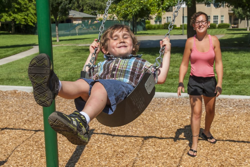 Resident and child playing on the playground at Oak Meadow Apartments in Chico, California