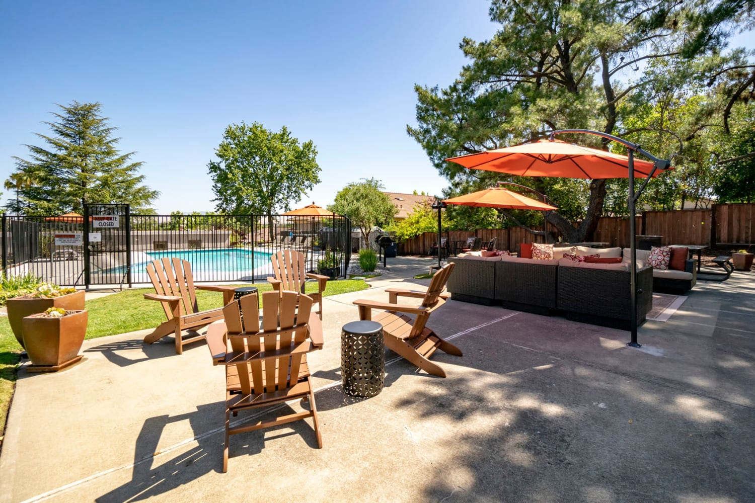 Barbecue area with Adirondack chairs with a view of the swimming pool at Pleasanton Heights in Pleasanton, California