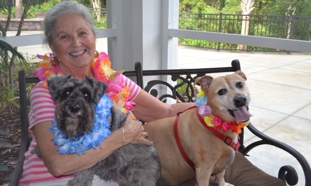 Resident of Cedarview Gracious Retirement Living posing with her dogs in Woodstock, Ontario