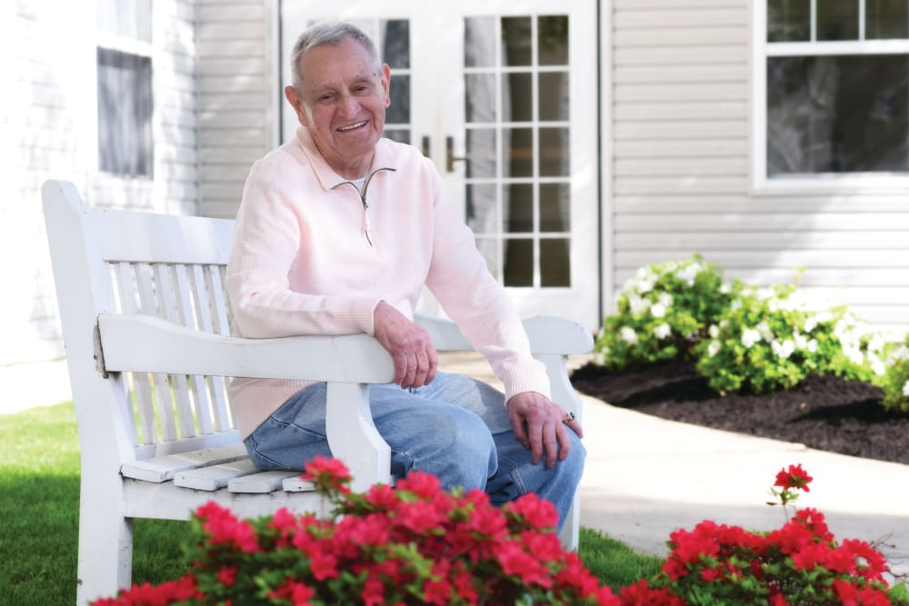 Man sitting in garden with flowers
