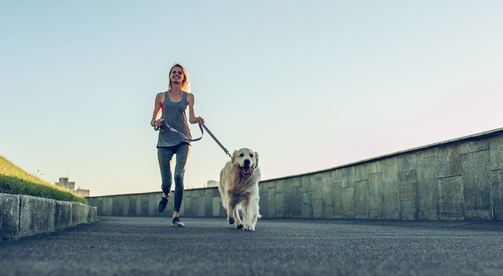 A resident running with her dog near Artisan Living Bella Citta in Davenport, Florida