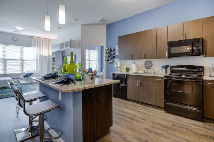 Modern kitchen with island in a model home at Celsius Apartment Homes in Charlotte, North Carolina