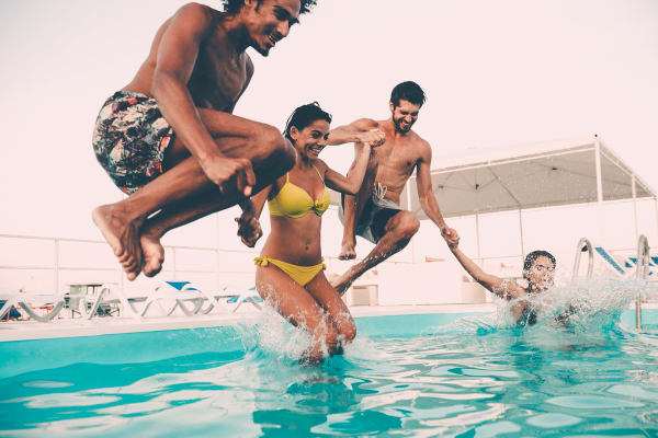 Friends jumping in the pool at Willow Oaks Apartments in Bryan, Texas