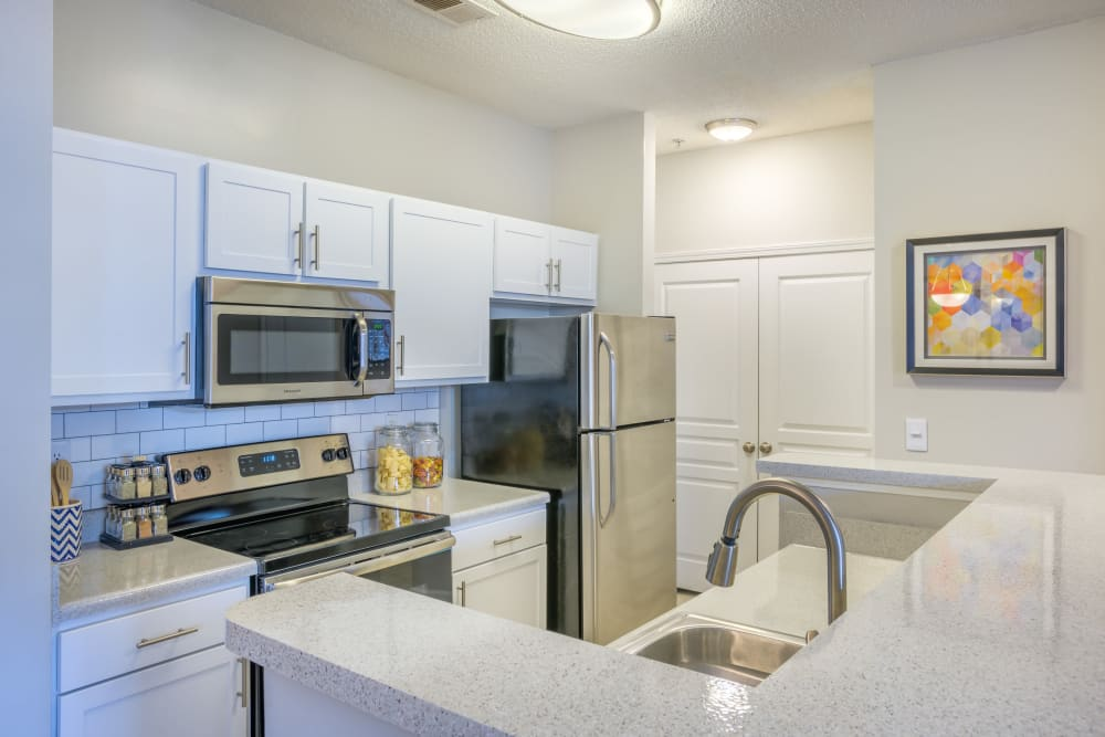 Bright white cabinetry in a model home's kitchen at The Avant at Steele Creek in Charlotte, North Carolina