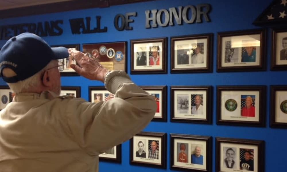 Veteran saluting the veterans' wall of honor with pride near Camden Springs Gracious Retirement Living in Elk Grove, California