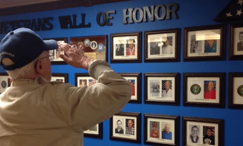 Veteran saluting the veterans' wall of honor near Ashwood Meadows Gracious Retirement Living in Johns Creek, Georgia