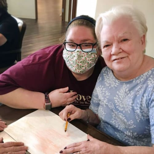Masked caretaker with a resident thats coloring The Oxford Grand Assisted Living & Memory Care in McKinney, Texas