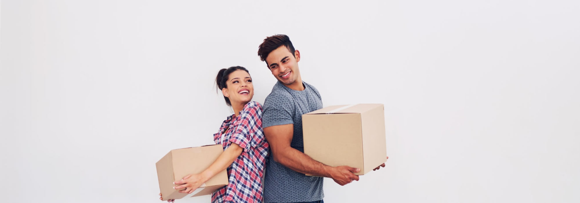 Couple holding packing boxes Self Storage Plus in Manassas, Virginia.