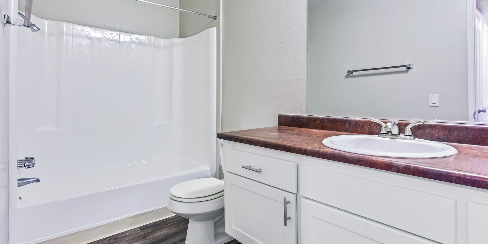 Bathroom with large vanity mirror at West Fifth Apartments in Ontario, California