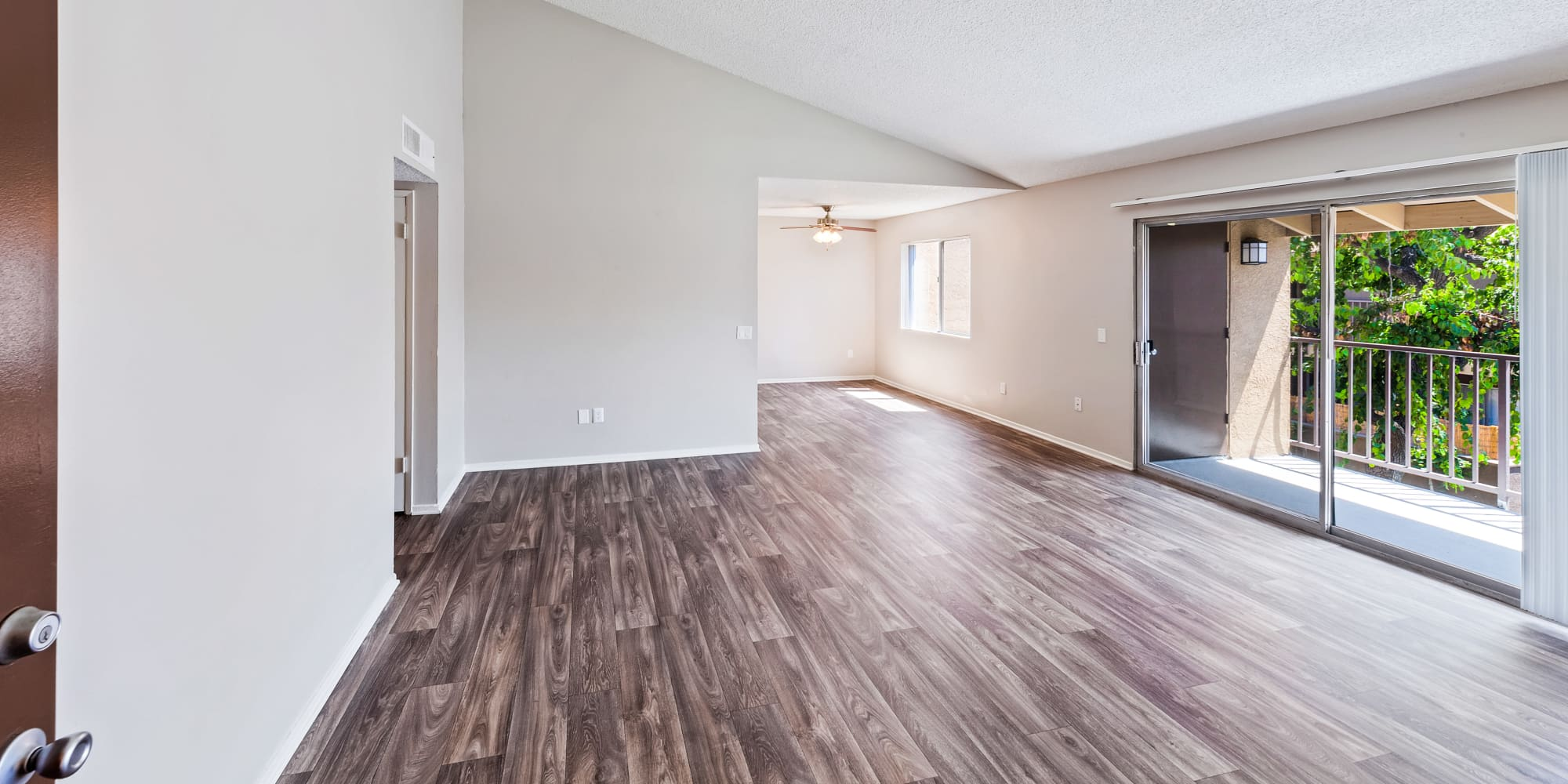 Spacious living room with hardwood floors at West Fifth Apartments in Ontario, California