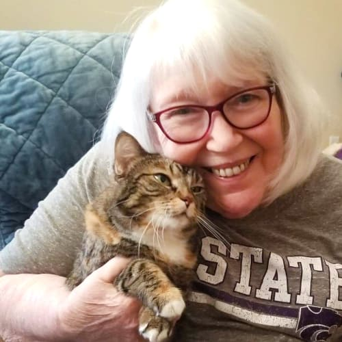 A smiling resident holding her pet cat at The Oxford Grand Assisted Living & Memory Care in Wichita, Kansas