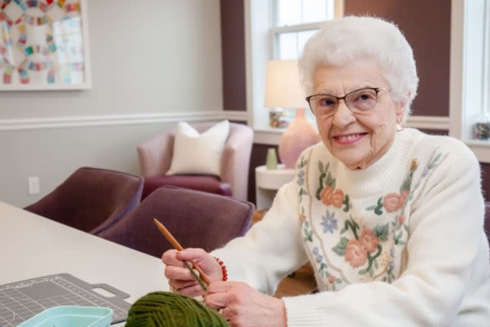A smiling resident knitting at Mercer Hill at Doylestown in Doylestown, Pennsylvania