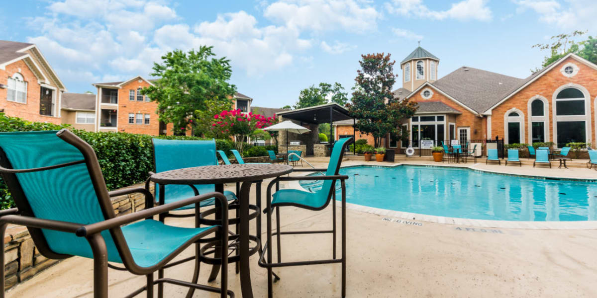 Lounge chairs and tables next to pool at Marquis at Kingwood in Kingwood, Texas