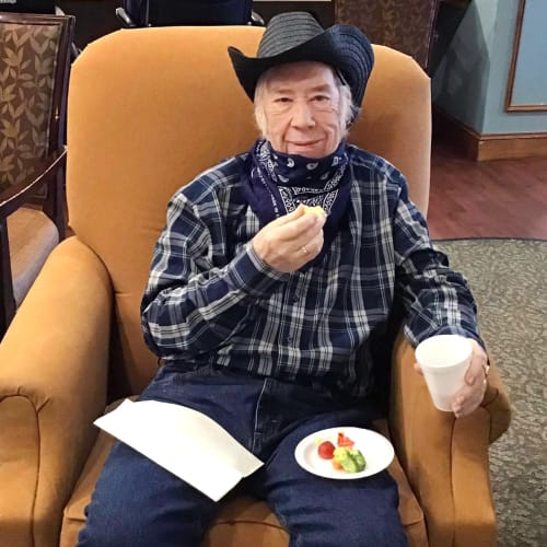 Seated resident with a fruit plate at Oxford Glen Memory Care at Grand Prairie in Grand Prairie, Texas