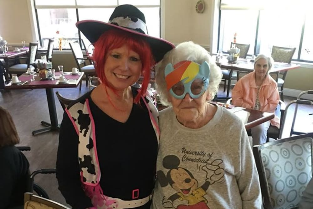 A resident and a care giver dressed fun for an event at Renaissance Retirement Center in Sanford, Florida