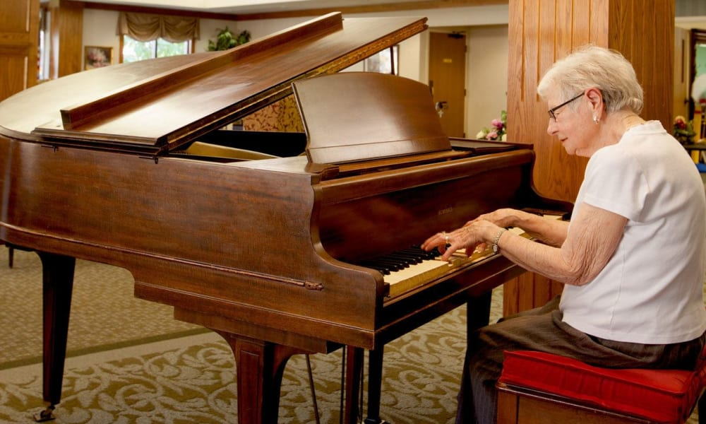 Resident playing the piano at Villa at the Lake in Conneaut, Ohio