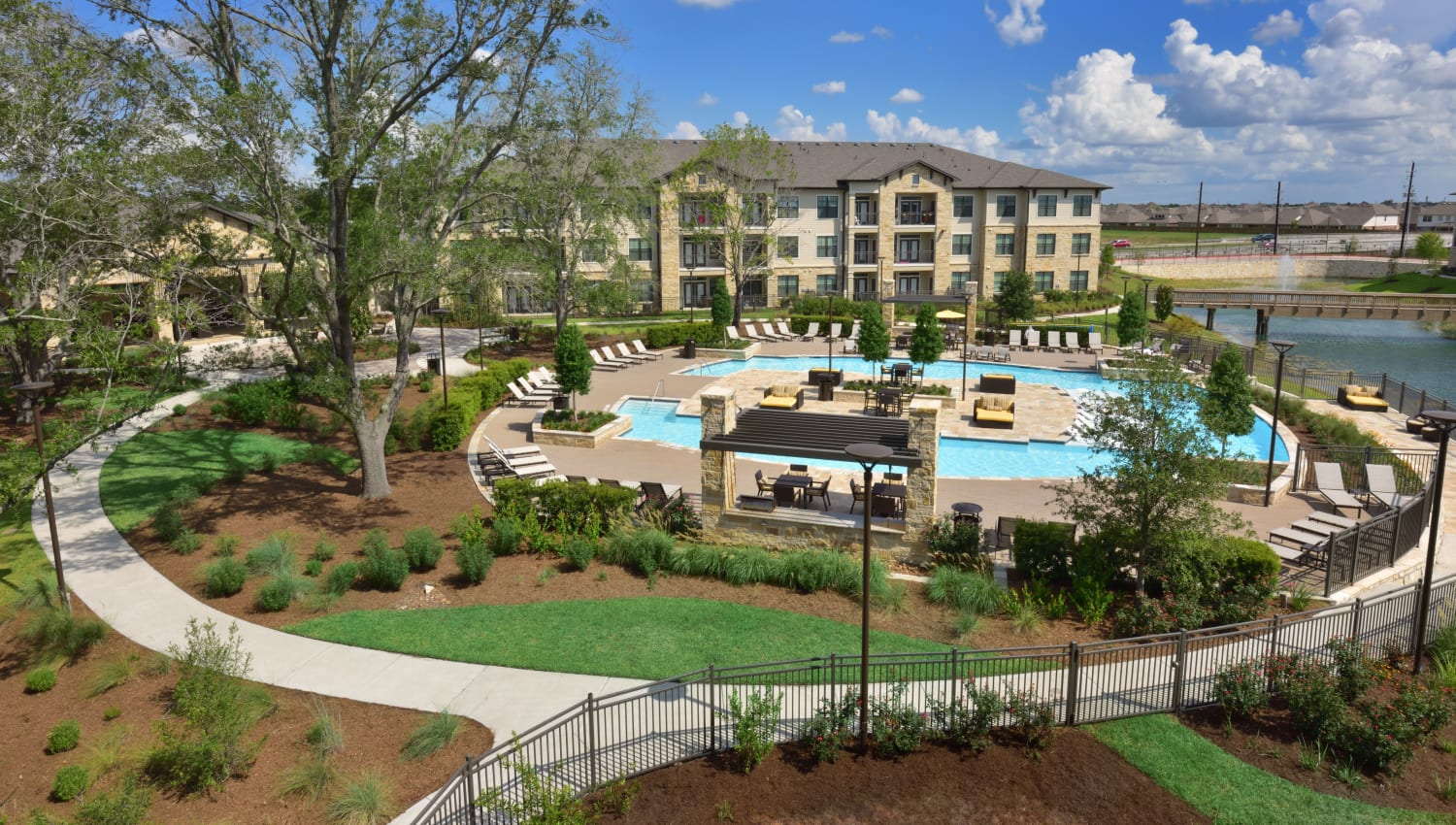 Community with a sparkling pool, walking paths and a lake at Olympus Falcon Landing in Katy, Texas