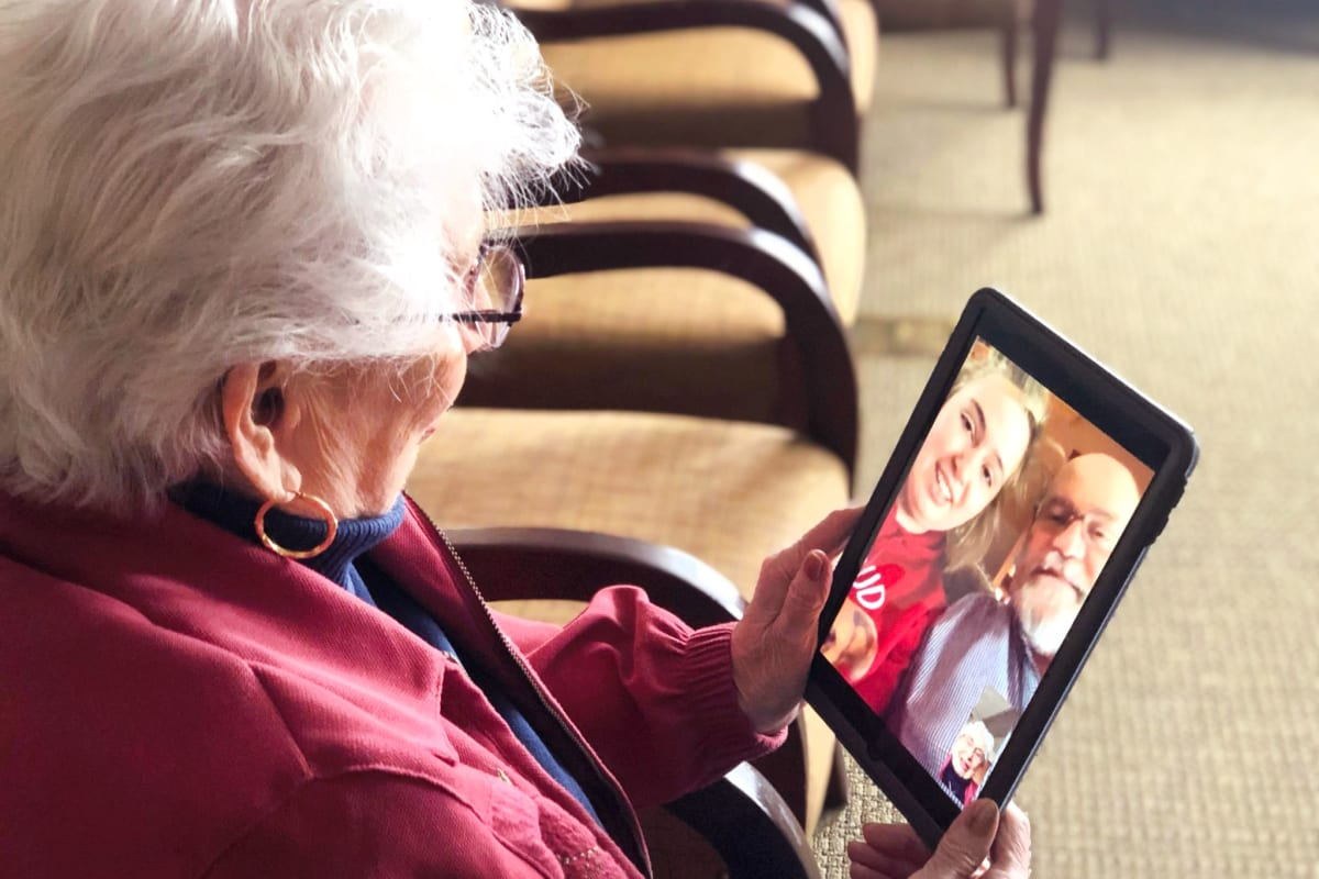A resident using a tablet at Oxford Glen Memory Care at Sachse in Sachse, Texas