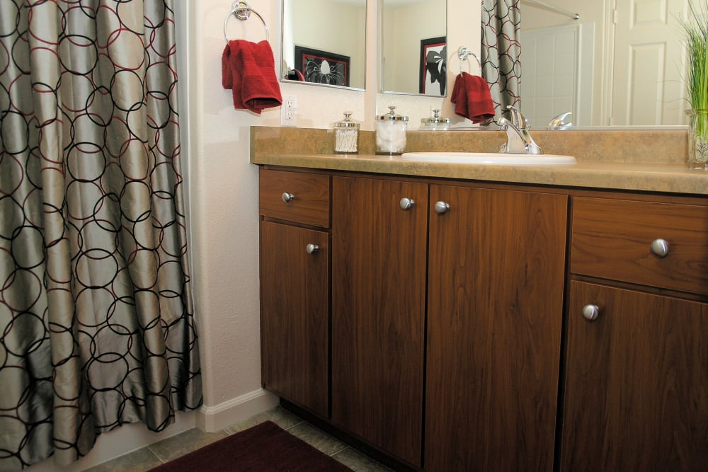 Model bathroom with wooden cabinetry at Venu at Galleria Condominium Rentals in Roseville, California