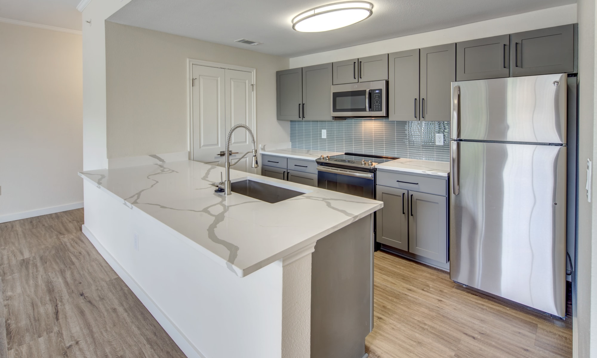 Stainless-steel appliances and quartz countertops in a model home's kitchen at Riata Austin in Austin, Texas