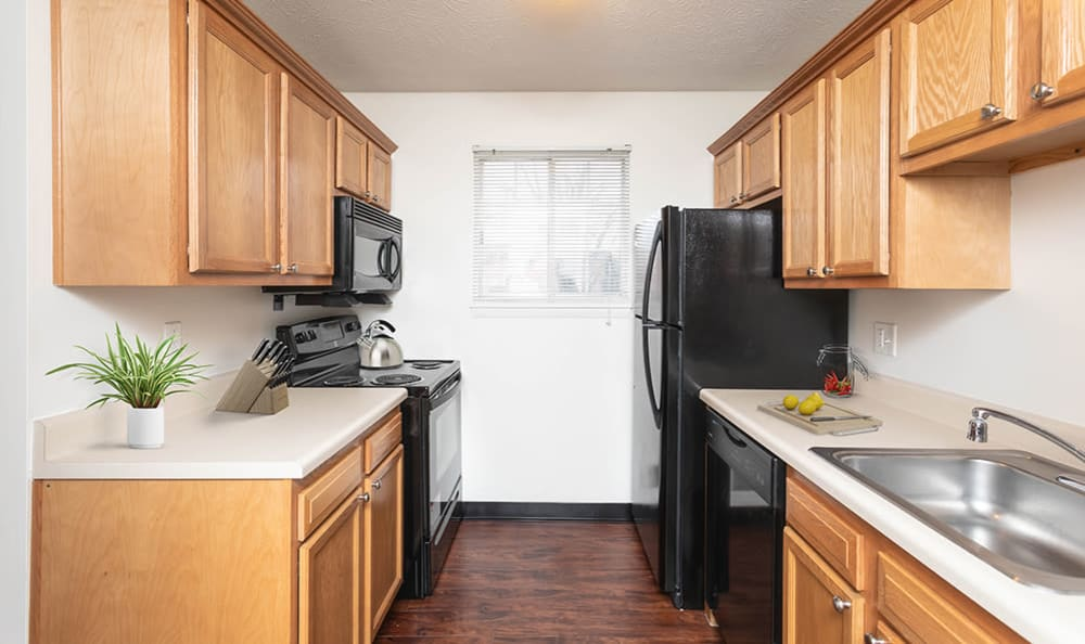 Kitchen with black appliances at Waverlywood Apartments & Townhomes in Webster, New York
