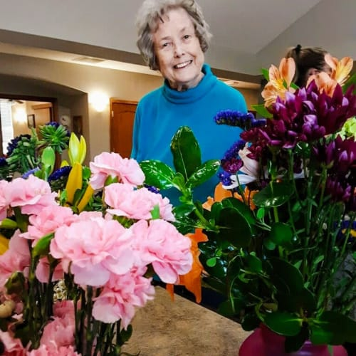A resident smiling with a collection of flowers at Glen Carr House Memory Care in Derby, Kansas