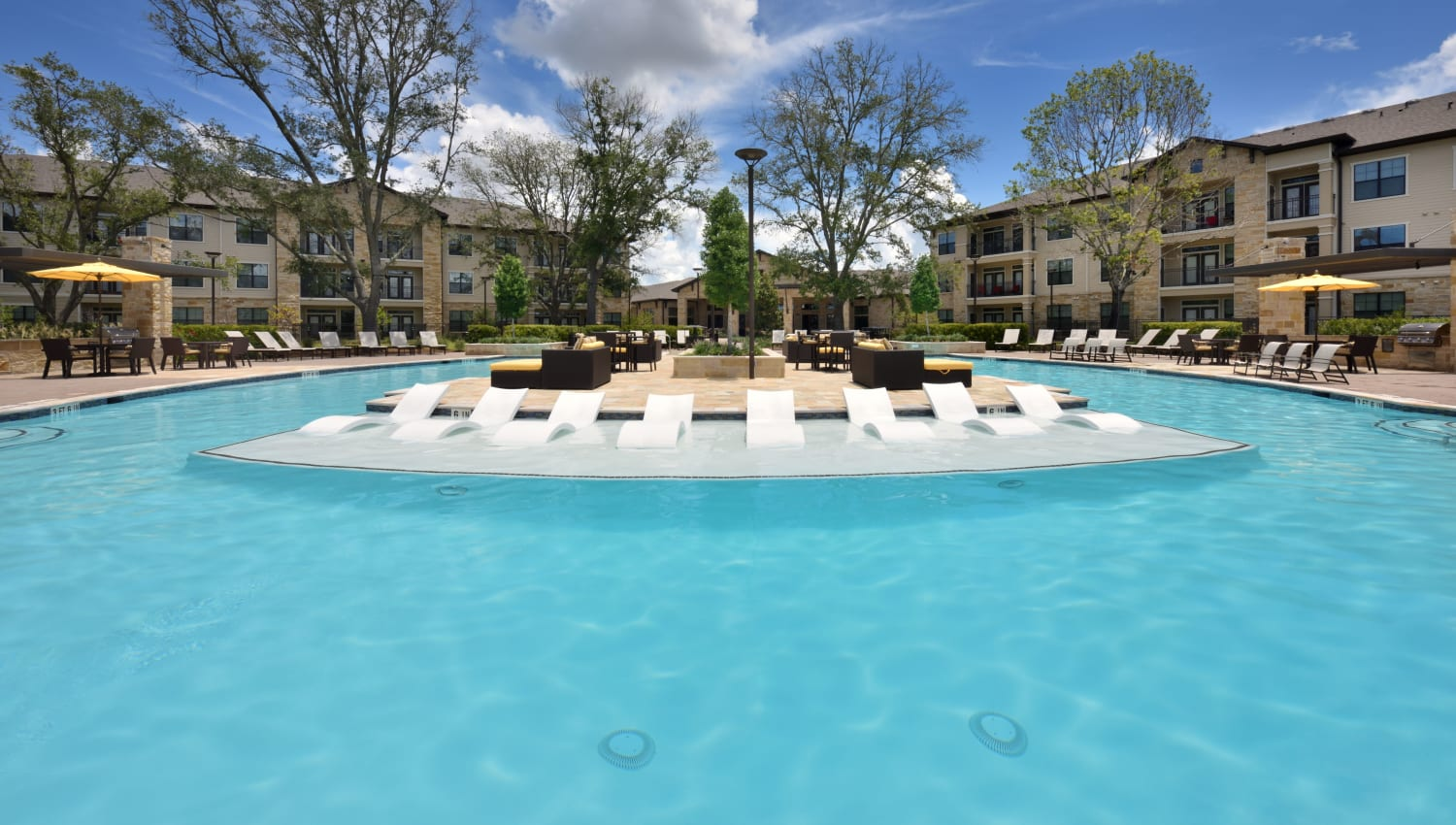 Sparkling pool with island with lounge chairs at Olympus Falcon Landing in Katy, Texas