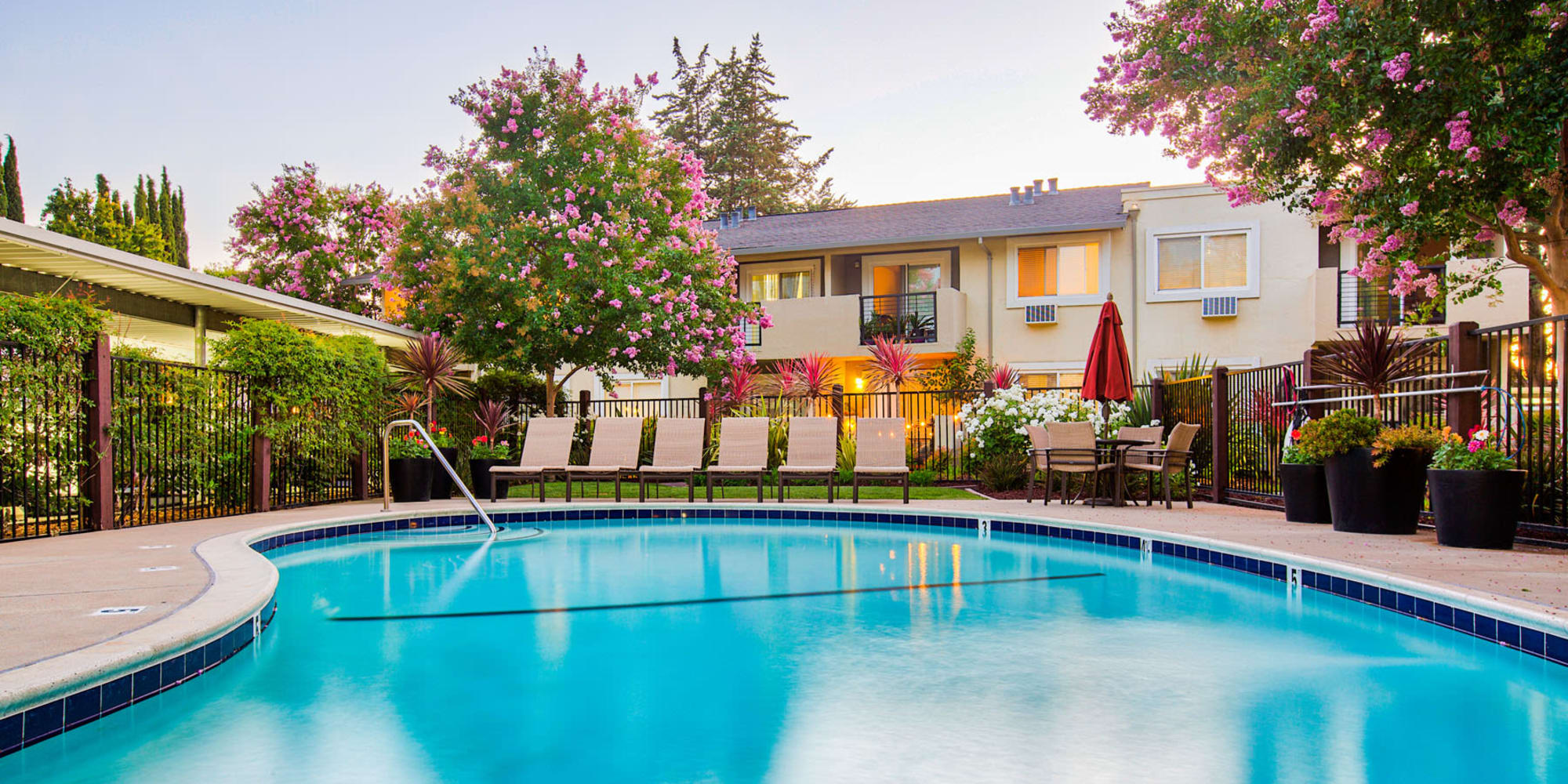 Early twilight view of the swimming pool area at Pleasanton Place Apartment Homes in Pleasanton, California