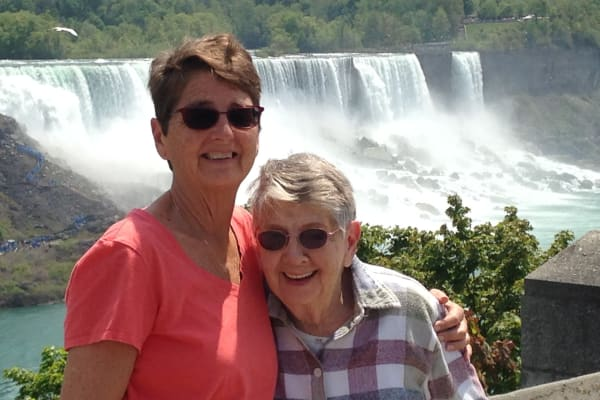 Edith and Sue from in front of a waterfall near Alexis Estates Gracious Retirement Living in Allen, Texas