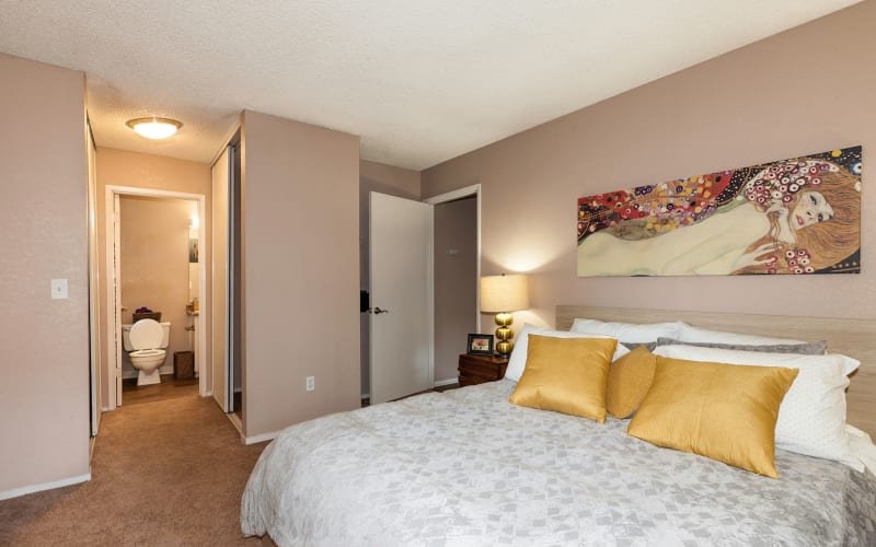 Spacious master bedroom with plush carpeting at The Woodlands Apartments in Sacramento, California