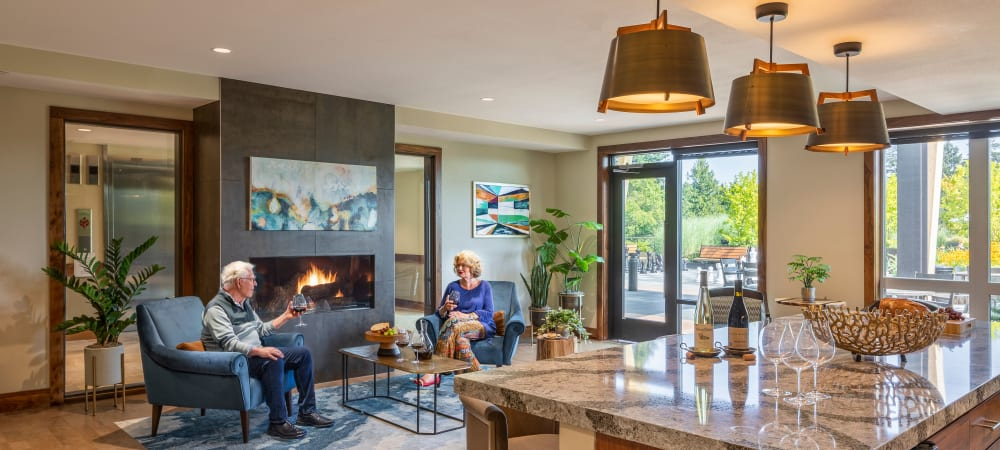 Two residents sitting by a fireplace at The Springs at Lake Oswego in Lake Oswego, Oregon