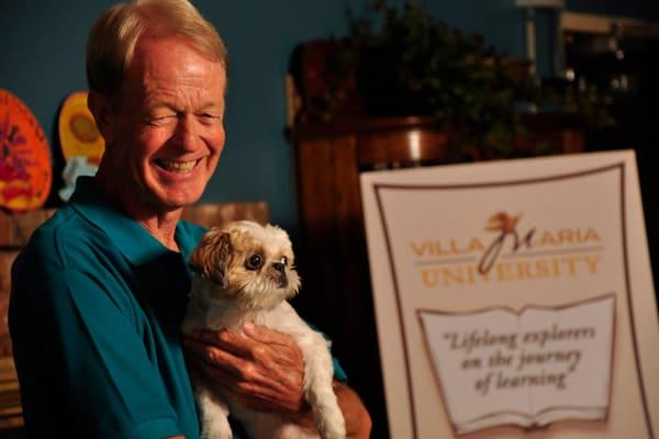 A senior holding a dog at Villa Maria Care Center in Tucson, Arizona