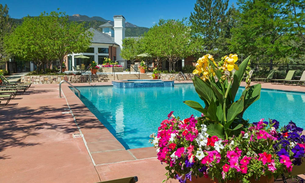 Sit by the swimming pool at Retreat at Cheyenne Mountain Apartments in Colorado Springs, Colorado