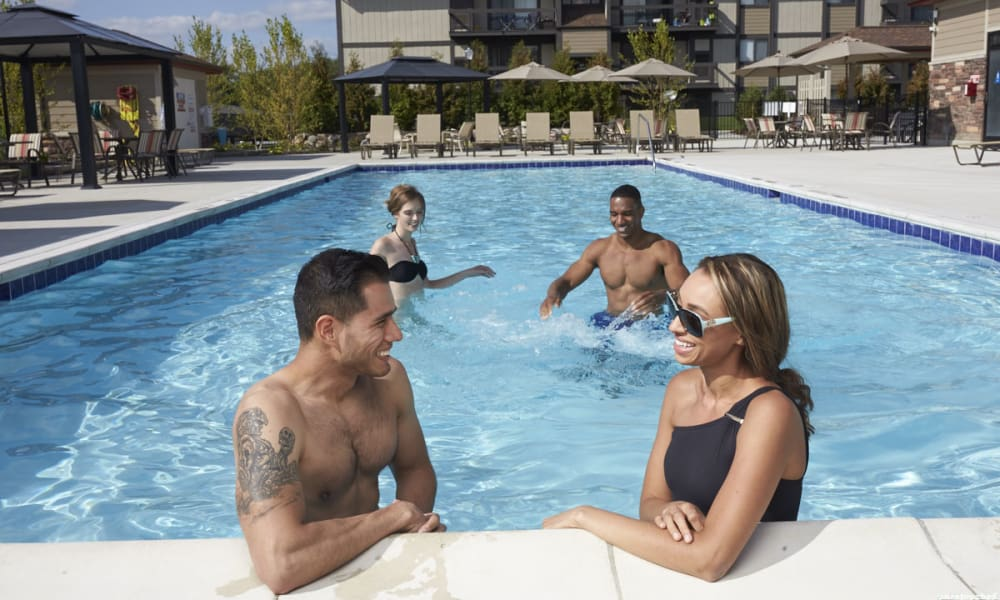 People happy by the pool at The Trilogy Apartments