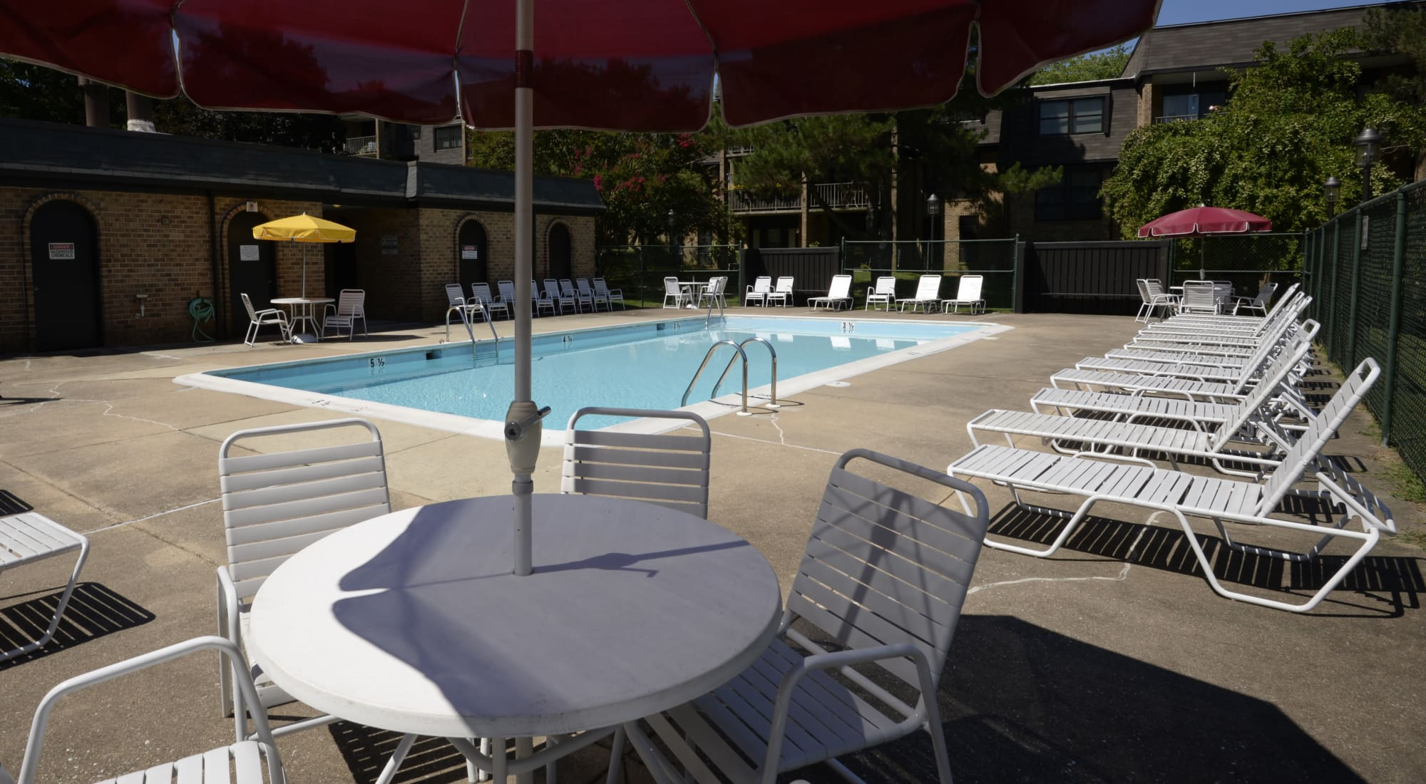 Swimming pools with chairs and a table at Charlesgate Apartments in Towson, Maryland
