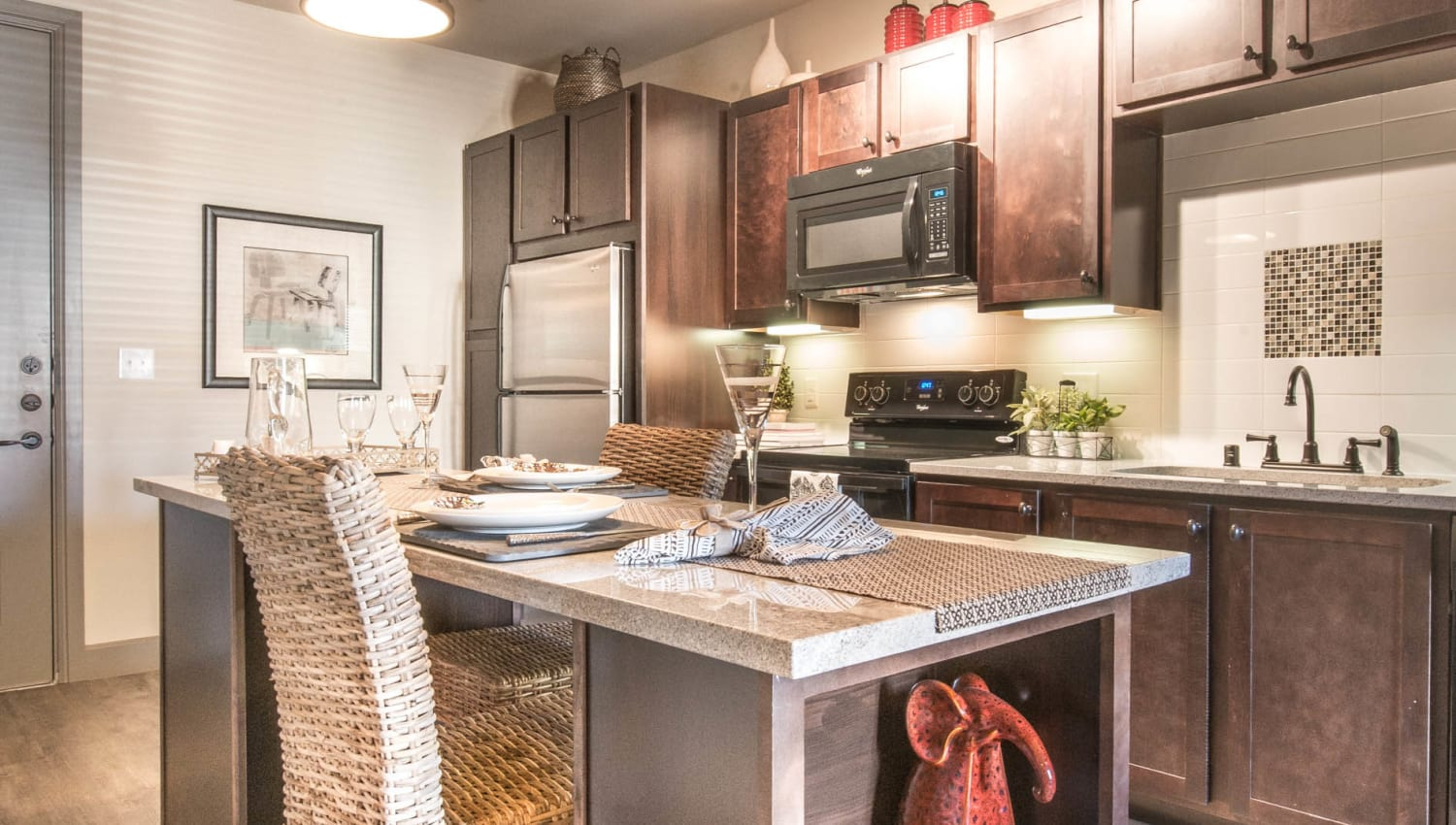 Seating area at the island in a model home's kitchen at Union At Carrollton Square in Carrollton, Texas