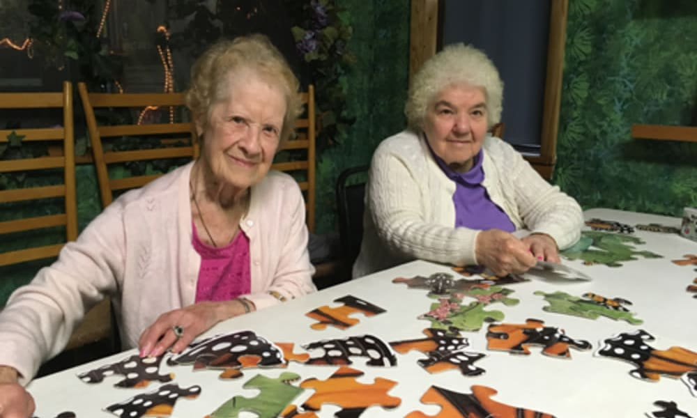 2 residents working on a puzzle at Heritage Hill Senior Community in Weatherly, Pennsylvania