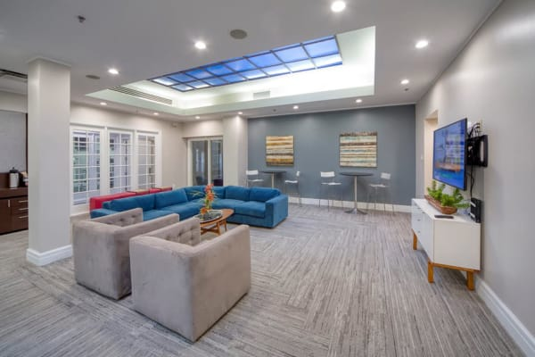 Modern lounge with square furniture and track lighting at WRH Realty Services, Inc